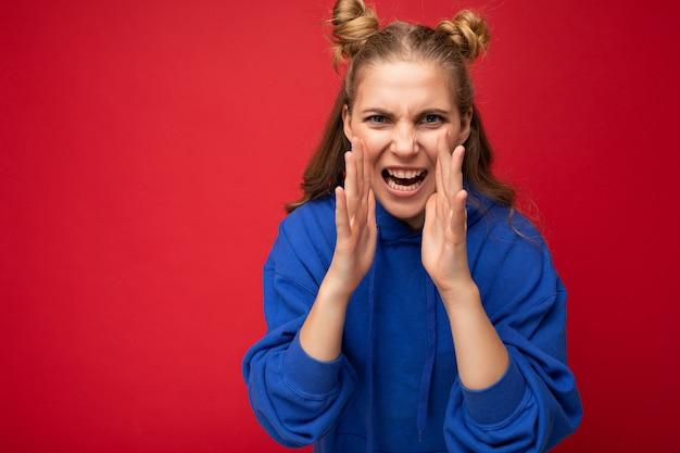 Foto der emotionalen verärgerten jungen schönen schönen blonden weiblichen person mit zwei hörnern mit aufrichtigen gefühlen, die trendigen hellblauen kapuzenpulli tragen, lokalisiert über rotem hintergrund mit leerem raum und schreien.