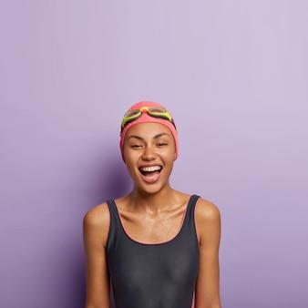 Foto der entspannten sorglosen afro-frau mit zahnigem lächeln, fühlt sich überglücklich