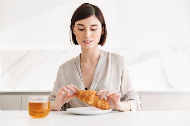 Foto der entzückenden morgenfrau, die im hotelzimmer frühstückt und croissant mit tee genießt