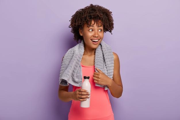 Foto der entzückten dunkelhäutigen sportlerin hat afro-haarschnitt, schaut mit einem lächeln zur seite, trägt ein rosa oberteil, trägt eine flasche, trinkt wasser, während sie sich während des trainings durstig fühlt, trainiert drinnen.