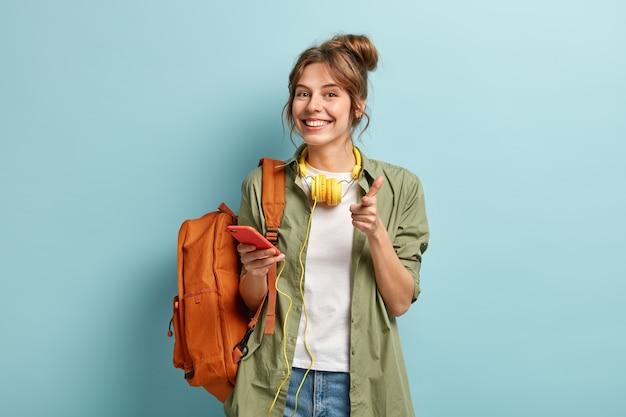 Foto der entzückten europäischen frau zeigt glücklich auf sie, hält smartphone-gerät an kopfhörer angeschlossen, nutzt musik-app