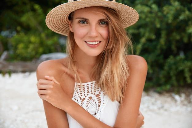 Foto der erfreuten attraktiven frau mit charmantem lächeln und herrlichem blick, trägt stilvollen strohhut, posiert im freien an der küste, badet in der sonne bei heißem sommerwetter. menschen, jahreszeit und ruhekonzept
