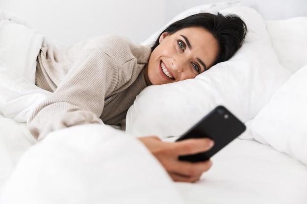 Foto der erfreuten frau 30s mit smartphone, während im bett mit weißer wäsche zu hause liegen