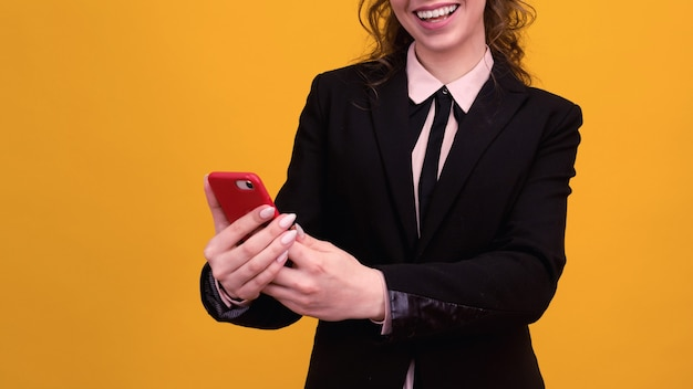 Foto der erfreuten jungen frau, die lokal über gelbe wand unter verwendung des mobiltelefons aufwirft.