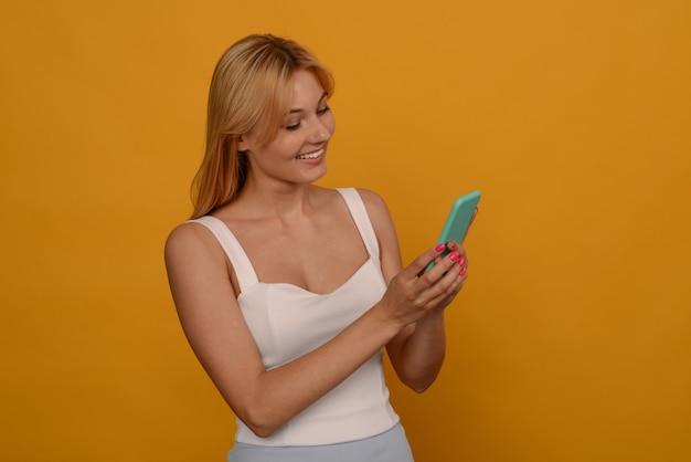 Foto der erfreuten jungen frau, die lokal über gelbem wandhintergrund unter verwendung des mobiltelefons aufwirft.