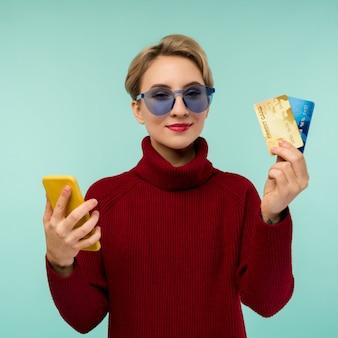 Foto der erfreuten jungen frau, die lokalisiert über blauem wandhintergrund unter verwendung der debitkarte des mobiltelefons hält.