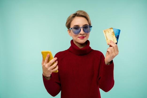 Foto der erfreuten jungen frau mit akneproblemgesichtshaut, die lokalisiert über blauem wandhintergrund unter verwendung des mobiltelefons hält, das debitkarte hält.