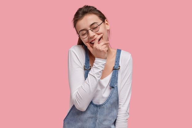 Foto der erfreuten lächelnden frau bedeckt mund, schließt augen vor vergnügen, kichert über guten witz, gekleidet in modische kleidung für die jugend
