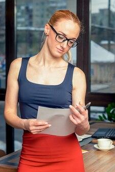Foto der ernsten frau trägt formelle kleidung und brillen, die in den papierdokumenten der hände halten, während sie im büro arbeiten