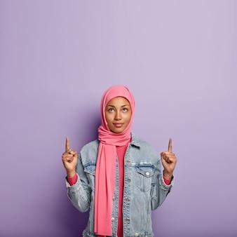 Foto der ernsten jungen muslimischen frau zeigt mit beiden vorderfingern nach oben, trägt rosa schal, trägt rosa und jeansjacke, isoliert über lila wand. menschen, werbung und verkaufsförderung.
