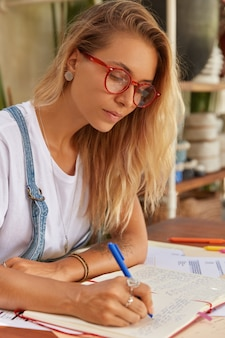 Foto der ernsthaften blonden journalistin trägt eine brille