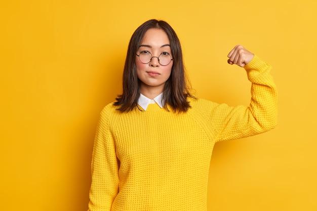 Foto der ernsthaften brünetten asiatischen frau hebt den arm und zeigt, dass ihre stärke starke muskeln hat, steht selbstbewusst drinnen, trägt gelben pullover und runde optische brille. frauenpower-konzept