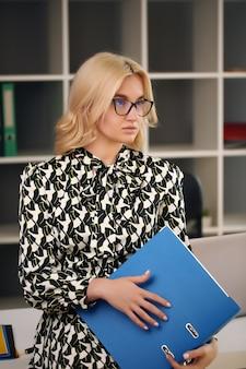 Foto der ernsthaften manager- oder direktorfrau, die formelle kleidung und brillen hält trägt