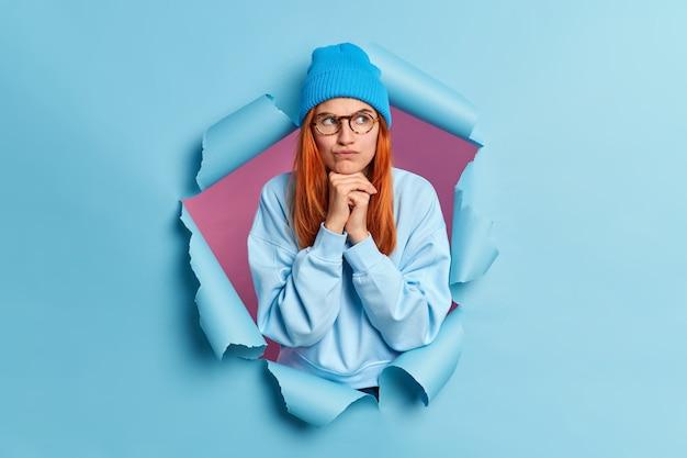 Foto der ernsthaften rothaarigen frau hält hände unter kinn sieht unzufrieden beiseite grinst gesicht mit unzufriedenheit trägt blauen pullover und hut bricht durch papierloch