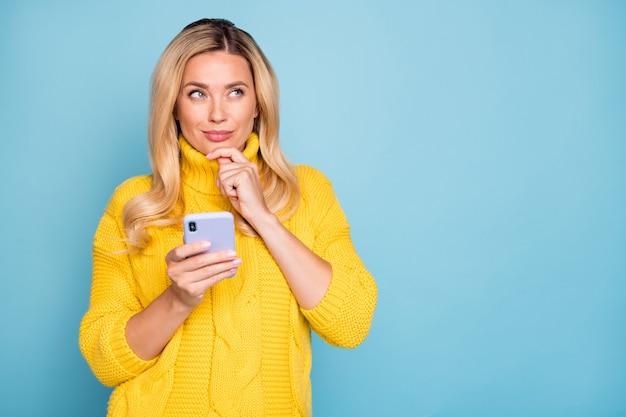 Foto der erstaunlichen blonden dame, die telefonhände hält, die über lustige fotokommentar denken, tragen gestrickten gelben pullover isolierte blaue farbwand