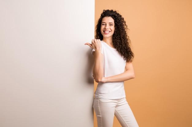Foto der erstaunlichen dame, die finger auf leerem rabattbanner anzeigt, der nahe dem großen weißen plakat steht, tragen weiße freizeitkleidung lokalisierten beige pastellfarbenhintergrund