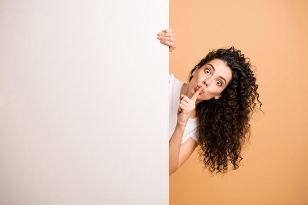 Foto der erstaunlichen dame, die leeres bannerplakat hält, das kunden fragt, nicht zu sagen, dass schwarzer freitag über finger auf lippen weiße freizeitkleidung isoliert beige pastellfarbenhintergrund trägt