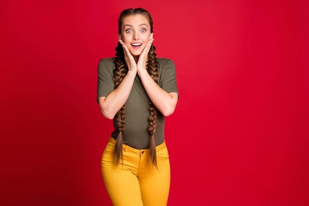 Foto der erstaunlichen dame lange zöpfe halten arme auf wangenknochen hören gute nachrichten letzte saison rabatte tragen lässige gelbe hosen grünes t-shirt isoliert rote farbe hintergrund