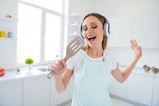 Foto der erstaunlichen hausfrau, die den morgen verbringt, musik moderne kopfhörer zu hören, die mischlöffel wie mikrofon halten, das weiße küche drinnen signiert