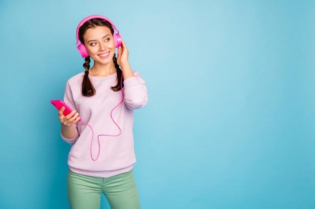 Foto der erstaunlichen hübschen dame, die telefon kühle helle kopfhörer auf ohren hält, die jugendradio hören, tragen lässige stilvolle rosa pulloverhose isolierte blaue farbe
