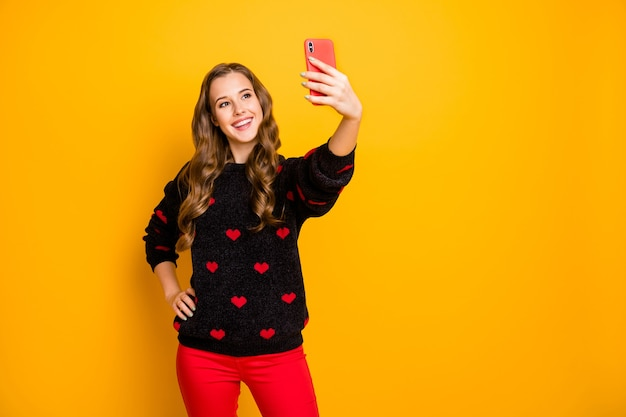 Foto der erstaunlichen hübschen dame halten telefonhände, die lustige positive energetische selfies machen, tragen herzmuster-pullover rote hosen