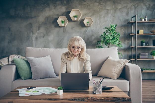 Foto der erstaunlichen weißhaarigen gealterten oma unter verwendung des notizbuchs, das e-mail liest, antwortet antwortpartnerpartner, die komfort sofa diwan wohnzimmer bürostil drinnen sitzen