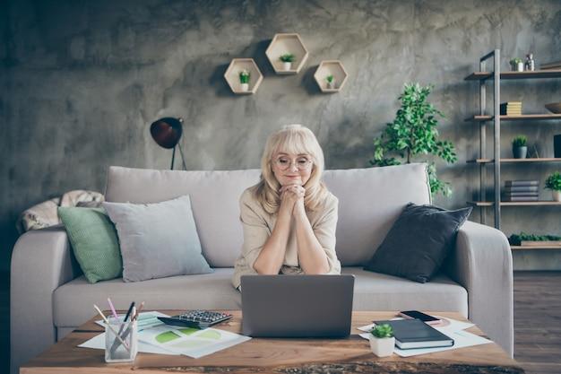Foto der erstaunlichen weißhaarigen gealterten oma unter verwendung des notizbuchs, das online-geschäftsvorlesungsstunde der meisterklasse spricht und skype-kollegen spricht, die drinnen im büro des diwanraums sitzen