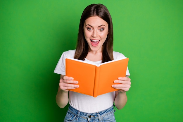 Foto der erstaunten süßen, fröhlichen brünetten dame, die ein buch liest, trägt weiße t-shirt-jeans einzeln auf grünem hintergrund
