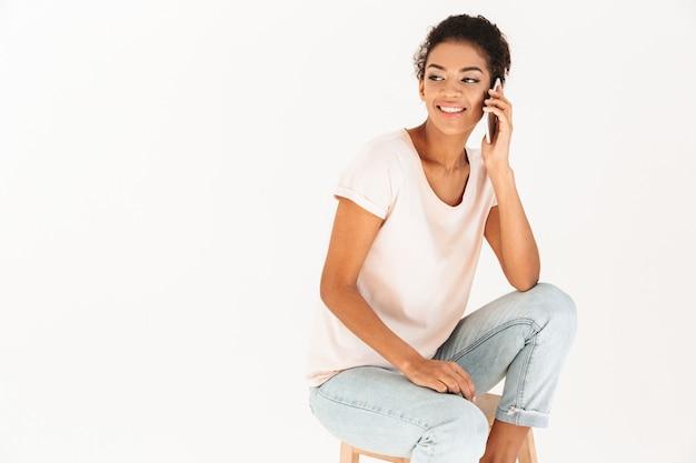 Foto der erwachsenen mischlingsfrau in der freizeitkleidung, die auf smartphone lächelt und spricht, lokalisiert über weißer wand