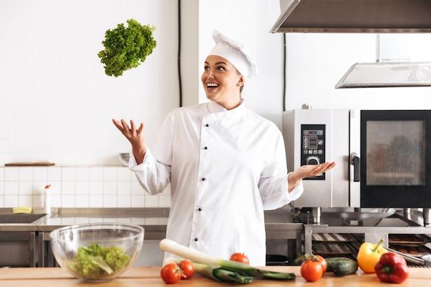 Foto der europäischen köchin, die weiße einheitliche kochmahlzeit mit frischem gemüse trägt, in der küche am restaurant