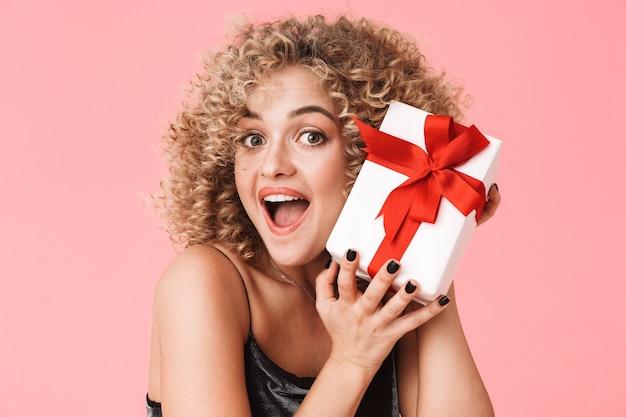 Foto der europäischen lockigen frau 20s, die kleid hält geschenkbox während des stehens