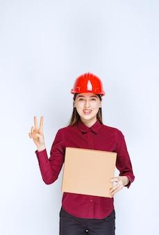 Foto der frau im roten helm, der kartonkasten hält und victory-zeichen gibt.