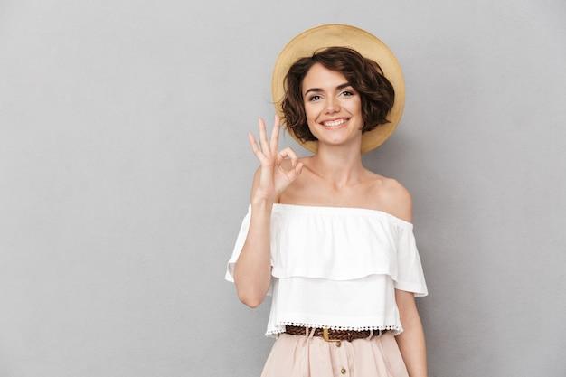Foto der freudigen brünetten frau 20s, die strohhut und sommerkleidung trägt, die sie betrachten und ok zeichen mit den fingern gestikuliert, lokalisiert über grauem hintergrund