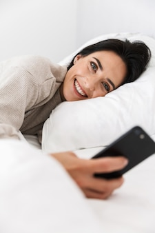 Foto der freudigen frau 30s mit smartphone, während im bett mit weißer wäsche zu hause liegen