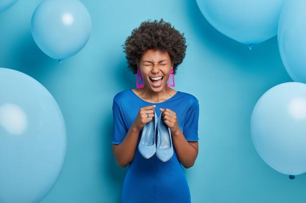 Foto der freudigen frau freut sich, neues outfit zu kaufen, hält blaue stilvolle schuhe passend zum kleid, kleidet sich zu besonderen anlässen und feiert geburtstag. blaue farbe herrscht vor. mode- und bekleidungskonzept