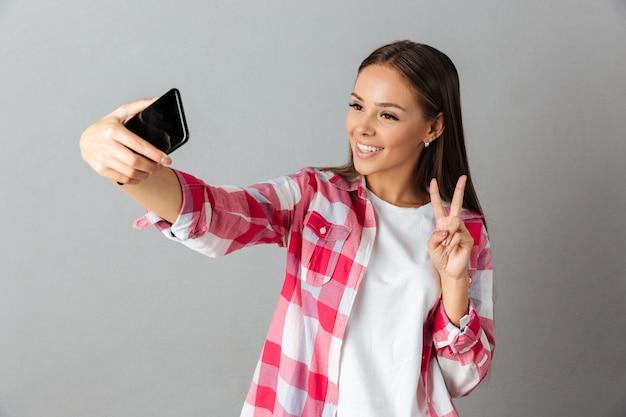 Foto der freudigen jungen frau im karierten hemd, selfie durch ihre telefone nehmend