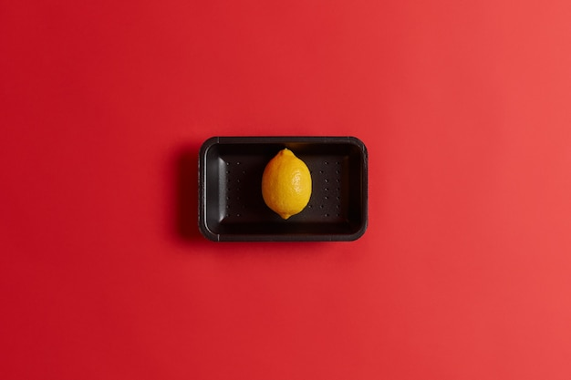 Foto der frischen reifen gelben einzelnen zitrone auf schwarzem tablett gekauft im supermarkt lokalisiert über rotem hintergrund. ganze exotische frucht mit viel vitamin c. zutat zum kochen von kalter sommerlimonade