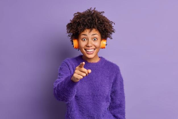 Foto der fröhlichen afroamerikanerin lächelt glücklich und zeigt direkt in die kamera fühlt sich sehr froh, dass sie kopfhörer auf den ohren tragen, hört lieblingsmusik