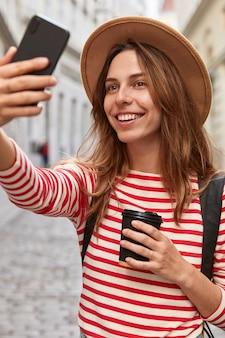 Foto der fröhlichen europäischen frau posiert für selfie, genießt spaziergang in der innenstadt, erholung im freien