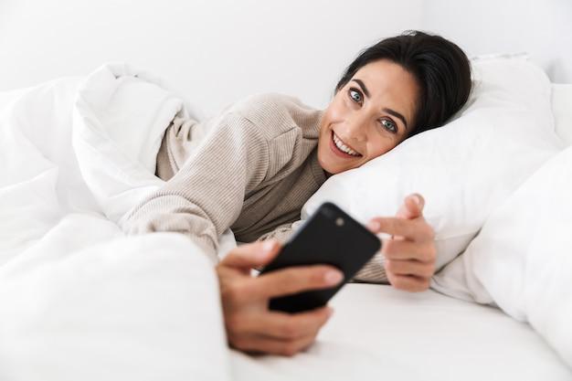 Foto der fröhlichen frau 30s mit smartphone, während im bett mit weißer wäsche zu hause liegen