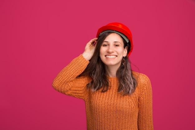 Foto der fröhlichen jungen frau, junger acrhitector, der einen schutzhelm trägt, der an der kamera lächelt und über rosa raum steht