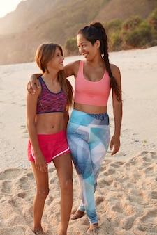Foto der fröhlichen mutter mit langem dunklem zopf, umarmt ihre jugendliche tochter, spazieren nach draußen, gekleidet in sportbekleidung