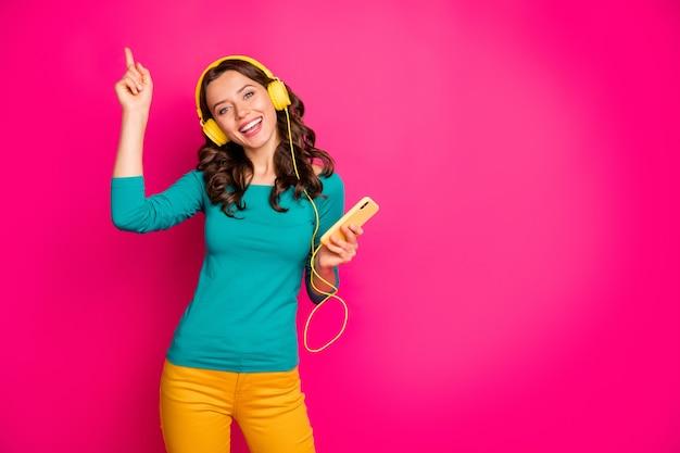 Foto der fröhlichen niedlichen hübschen süßen freundin, die in der gelben hosenhose tanzt, die sich freut, altes lied gefunden zu haben, das sie gern über rosa lebendigen farbhintergrund isoliert hat