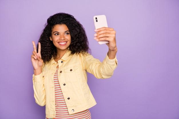 Foto der fröhlichen positiven funky niedlichen hübschen charmanten freundin, die vsign tragen gelbes hemd zeigt, das selfie isolierten violetten pastellfarbhintergrund nimmt