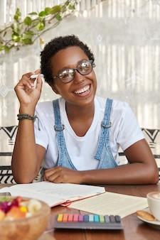 Foto der fröhlichen schwarzen frau mit breitem lächeln, denkt über lösungsidee nach