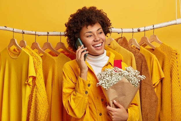 Foto der frohen frau in der leuchtend gelben jacke, steht gegen kleider auf kleiderbügeln in ihrem hausgarderobe, bereit zum ausgehen, ruft freund über mobilfunkstrauß an. weiblicher shopaholic mag gelbe farbe