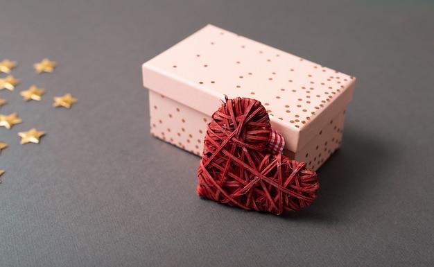 Foto der geschenkbox mit rotem herzen auf dunklem tisch