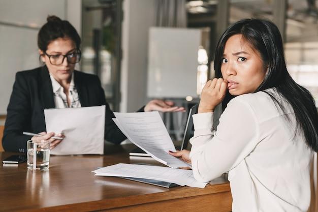 Foto der gestressten asiatischen frau, die panik ausdrückt, während sie am tisch im büro sitzt und mit weiblicher mitarbeiterin während des vorstellungsgesprächs spricht - geschäfts-, karriere- und rekrutierungskonzept