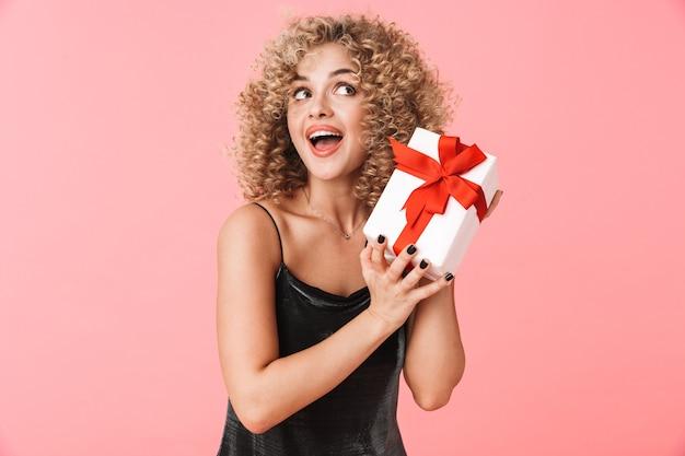 Foto der glamourösen lockigen frau 20s, die kleid hält geschenkbox während des stehens