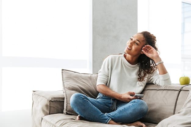 Foto der glücklichen afroamerikanerfrau, die handy verwendet, während auf der couch in der hellen wohnung sitzend